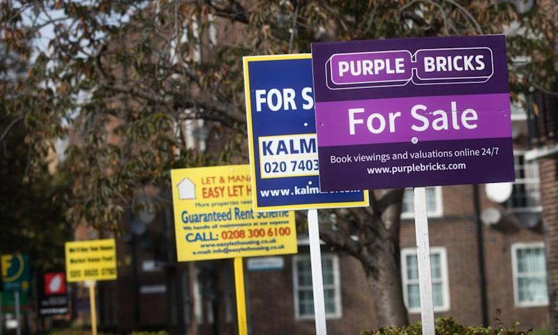 Estate agents' boards advertising homes for sale stand near a block of flats in London