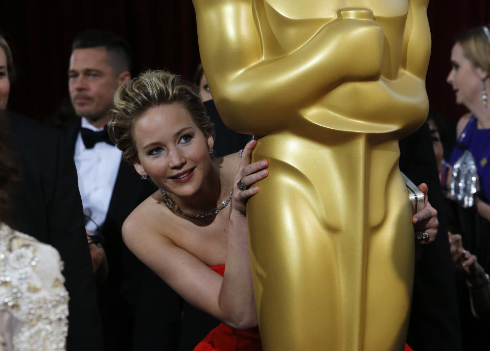 "Jennifer Lawrence, best supporting actress nominee for her role in the film ""American Hustle"", peeks around an Oscar statue on the red carpet as actor Brad Pitt (L) looks on at the 86th Academy Awards in Hollywood, California March 2, 2014. REUTERS/Adrees Latif (UNITED STATES  - Tags: ENTERTAINMENT)(OSCARS-ARRIVALS)"