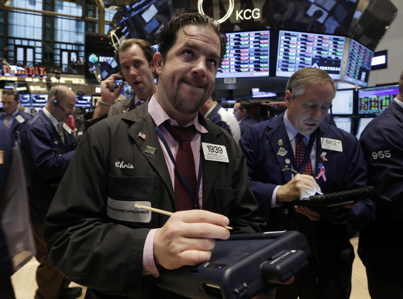 Trader Christopher Lotito, center, works on the floor of the New York Stock Exchange Thursday, Oct. 31, 2013. Stocks edged lower in early trading on Wall Street Thursday, paring the market's big gain for October. (AP Photo/Richard Drew)