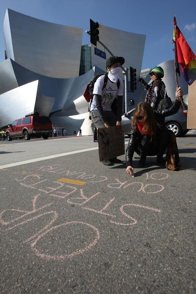 LOS ANGELES, CA - NOVEMBER 5:  An Occupy LA protester writes a message in chalk in front of Disney Hall during the Move Your Money March on what is being called Bank Transfer Day on November 5, 2011 in Los Angeles, California. Occupy movement members are calling for people to move their money from banks to credit unions today in support of the 99% movement.   (Photo by David McNew/Getty Images)