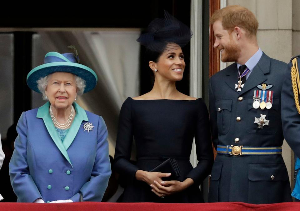 Britain's Queen Elizabeth II, and Meghan the Duchess of Sussex and Prince Harry (AP)