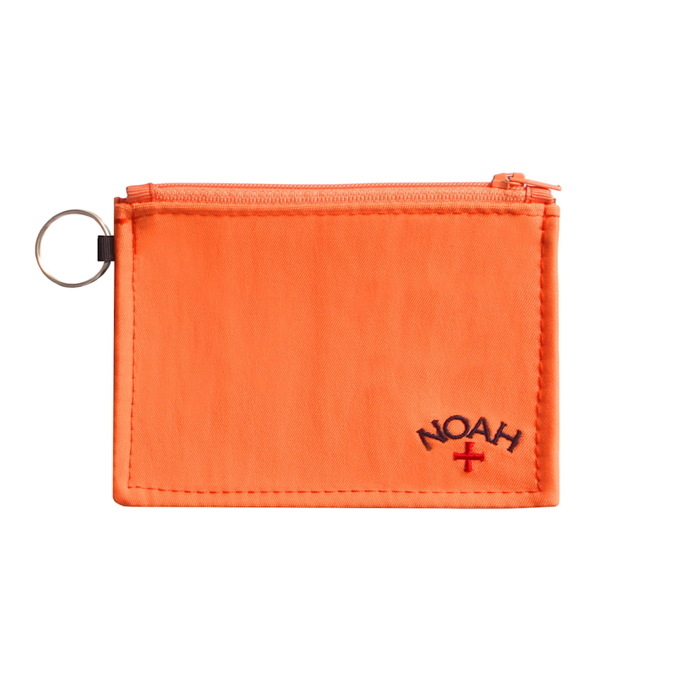 """Keep your money dry and your wallet stylish with this neon orange card carrier courtesy of NYC's skate and surf brand Noah. <br> <br> <strong>Noah NYC</strong> Water Resistant Pouch, $, available at <a href=""""https://go.skimresources.com/?id=30283X879131&url=https%3A%2F%2Fnoahny.com%2Fcollections%2Faccessories%2Fproducts%2Fwater-resistant-pouch-small"""" rel=""""nofollow noopener"""" target=""""_blank"""" data-ylk=""""slk:Noah NYC"""" class=""""link rapid-noclick-resp"""">Noah NYC</a>"""