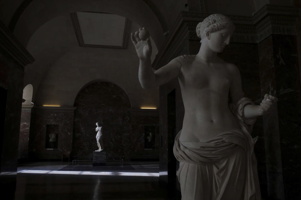 The Venus of Milo sculpture, background, is lit by a ray of light in the Louvre museum, in Paris, Thursday, Feb. 11, 2021. It's uncertain when the Louvre will reopen, after being closed on Oct. 30 in line with the French government's virus containment measures. But those lucky enough to get in benefit from a rarified private look of collections covering 9,000 years of human history -- with plenty of space to breathe. (AP Photo/Thibault Camus)