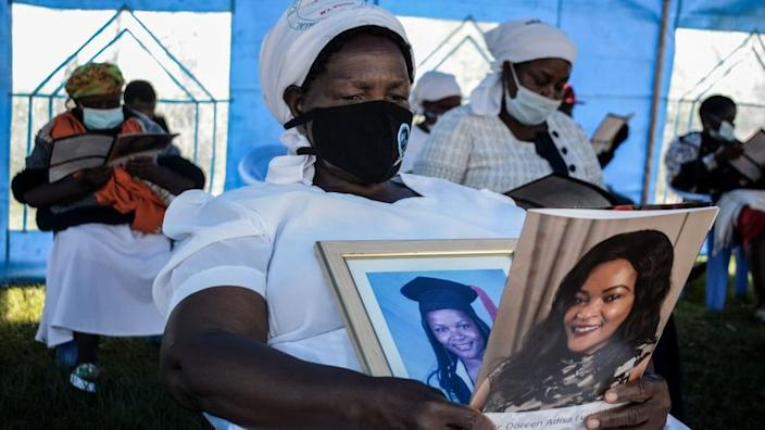 Grace Lugaliki holds portraits of her daughter Dr Doreen Lugaliki, 39, the first Kenyan doctor to die of Covid-19