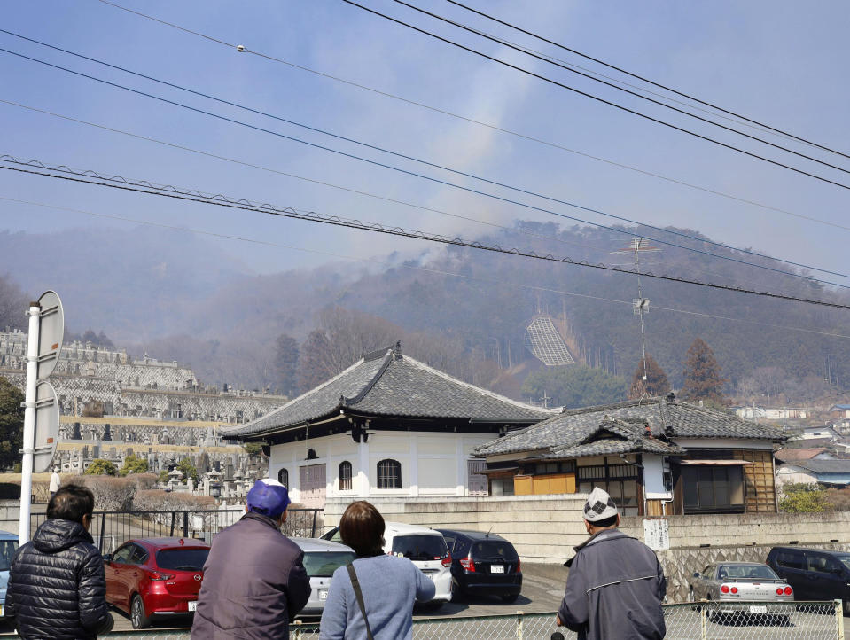 Residents watch as smoke rises from the site of a wildfire in Ashikaga, Tochigi prefecture, north of Tokyo Wednesday, Feb. 24, 2021. A forest fire broke out in the rural area Thursday, near another blaze burning since Sunday, Feb. 21. (Kyodo News via AP)