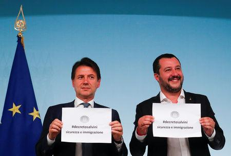 Italy's Prime Minister Giuseppe Conte and Interior Minister Matteo Salvini hold up pieces of paper with the name of the new decree written on them during a news conference at Chigi Palace in Rome, Italy, September 24, 2018.   REUTERS/Alessandro Bianchi