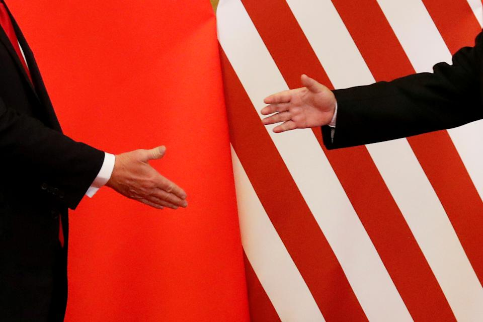 """U.S. President Donald Trump and China's President Xi Jinping shake hands after making joint statements at the Great Hall of the People in Beijing, China, November 9, 2017. Damir Sagolj: """"It's one of those """"how to make a better or at least different shot when two presidents shake hands several times a day, several days in row"""". If I'm not mistaken in calculation, presidents Xi Jinping of China and Donald Trump of the U.S. shook their hands at least six times in events I covered during Trump's recent visit to China. I would imagine there were some more handshakes I haven't seen but other photographers did. And they all look similar - two big men, smiling and heartily greeting each other until everyone gets their shot. But then there is always something that can make it special - in this case the background made of U.S. and Chinese flags. They shook hands twice in front of it, and the first time it didn't work for me. The second time I positioned myself lower and centrally, and used the longest lens I have to capture only hands reaching for a handshake."""" REUTERS/Damir Sagolj/File Photo  SEARCH """"POY TRUMP"""" FOR THIS STORY. SEARCH """"REUTERS POY"""" FOR ALL BEST OF 2017 PACKAGES.    TPX IMAGES OF THE DAY"""