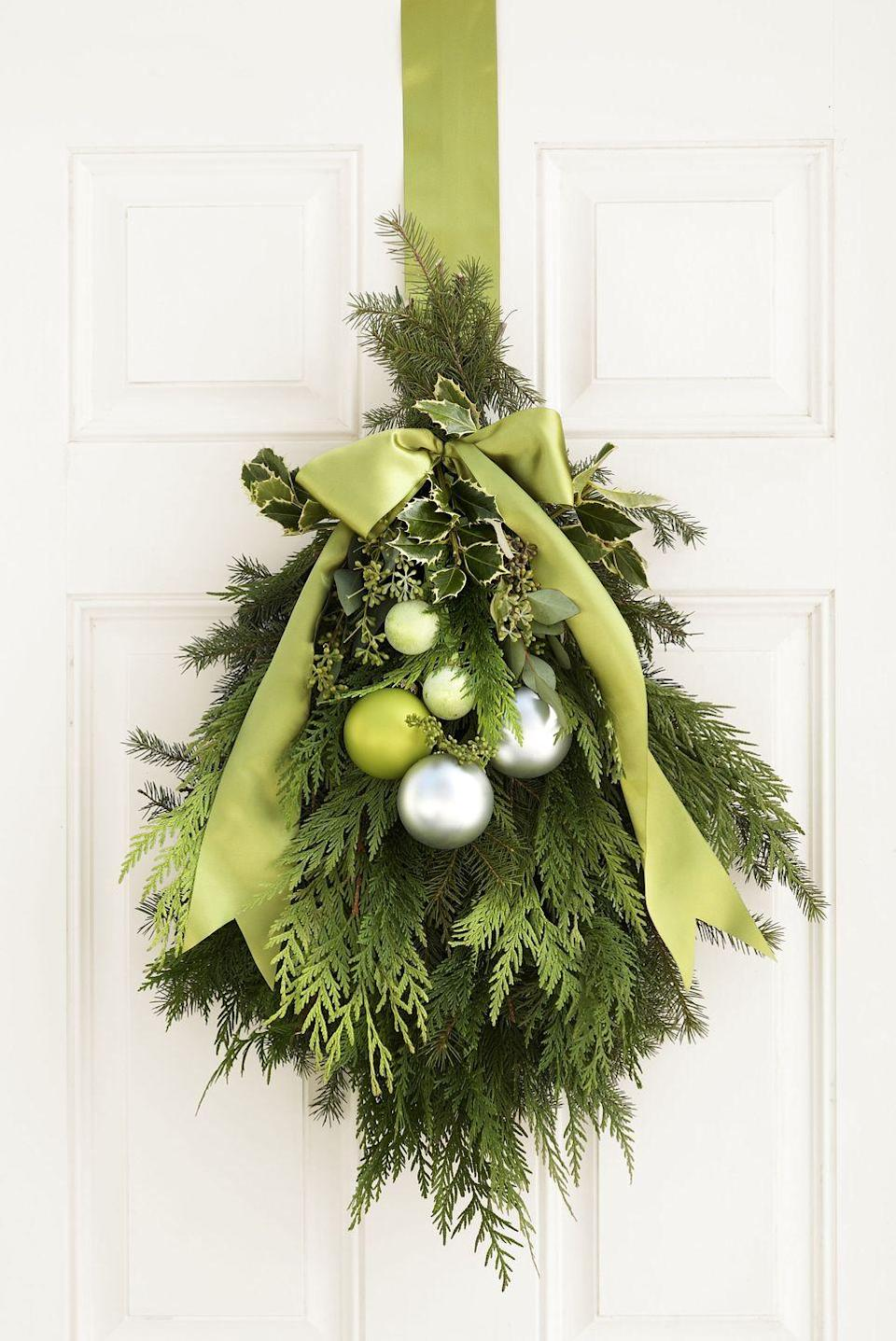 <p>Your door decoration doesn't have be a wreath, you know. Bundled together with floral wire, fragrant greenery — yew, holly, spruce, and eucalyptus — make a grand entrance. </p>
