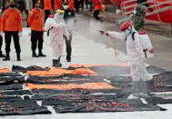 Members of Indonesian Red Cross spray disinfectant at body bags containing human remains retrieved from from the Java Sea where Sriwijaya Air flight SJ-182 crashed on Saturday, at Tanjung Priok Port in Jakarta, Indonesia, Thursday, Jan. 14, 2021. An aerial search for victims and wreckage of a crashed Indonesian plane expanded Thursday as divers continued combing the debris-littered seabed looking for the cockpit voice recorder from the lost Sriwijaya Air jet. (AP Photo/Dita Alangkara)