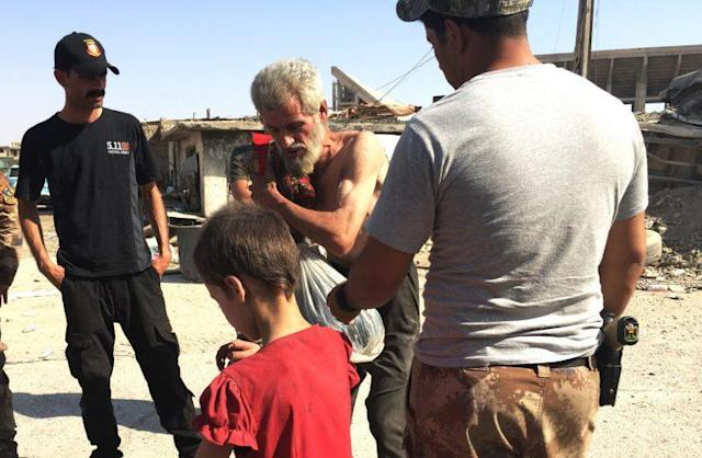 Displaced people fleeing Mosul are questioned and checked with hidden explosives by Iraqi security forces. (Ash Gallagher for Yahoo News)