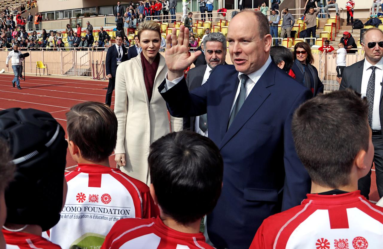 Prince Albert II greets Monaco's rugby team as Princess Charlene of Monaco looks on before the start of the Sainte Devote rugby tournament in collaboration with Princess Charlene Foundation at Louis II Stadium in Monaco March 18, 2017.               REUTERS/Eric Gaillard