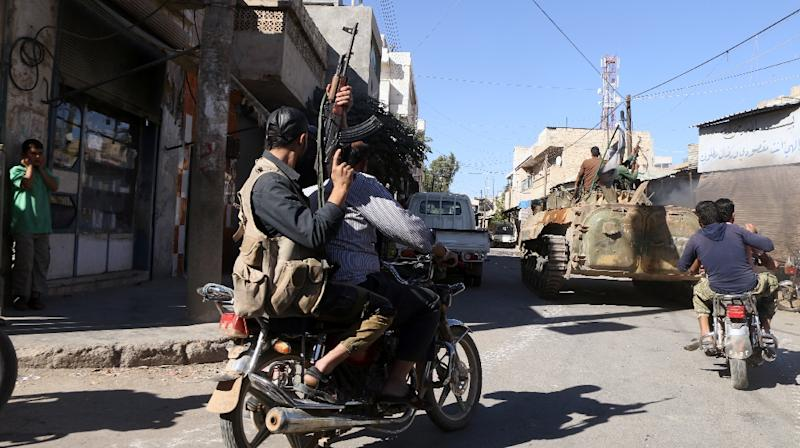 Rebel fighters celebrate their capturing of the town of Dabiq in the streets of the northern Syrian town of Marea, on October 16, 2016 (AFP Photo/Nazeer al-Khatib)