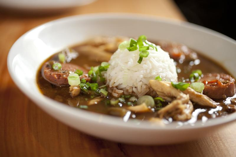 Close up of delicious, hearty chicken gumbo with big chunks of chicken and thick slices of andouille sausage. finished off with a scoop of rice in the middle.