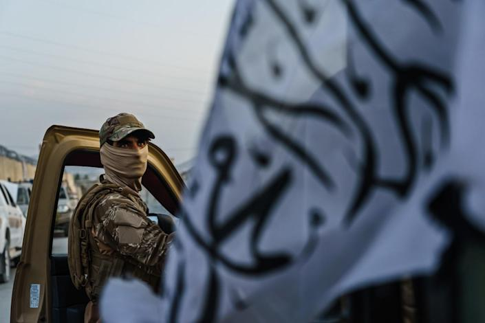 A Taliban fighter appears in the open door of a vehicle next to a white Taliban flag