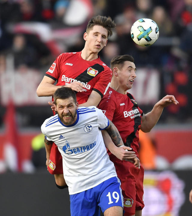 Schalke's Guido Burgstaller, down, Leverkusen's Panagiotis Retsos and Leverkusen's Dominik Kohr, right, challenge for the ball during the German Bundesliga soccer match between Bayer Leverkusen and FC Schalke 04 in Leverkusen, Germany, Sunday, Feb 25, 2018. (AP Photo/Martin Meissner)
