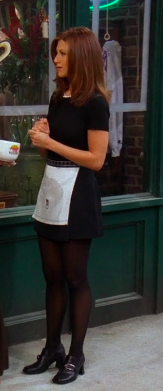 Rachel wearing small heeled boots, tights, a skirt, an apron, and a shirt