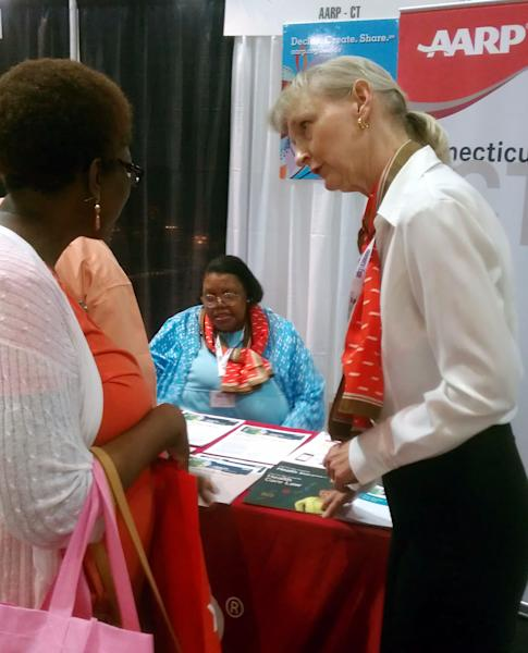 In this image made available by AARP shows Ida Gall, right speaking to an unidentified customer at the Connecticut Women's Expo on Saturday, Sept. 7, 2013 in Hartford, CT. AARP Connecticut volunteers Ida Gall and Sophia Forbes, seated, talked to women about the Affordable Care Act. Federal Health Officials are assuring medicare recipients that their benefits will not change when the Affordable Care Act starts. Many are confused by overlapping enrollment periods for Medicare and the Affordable Care Act. (AP Photo/AARP)