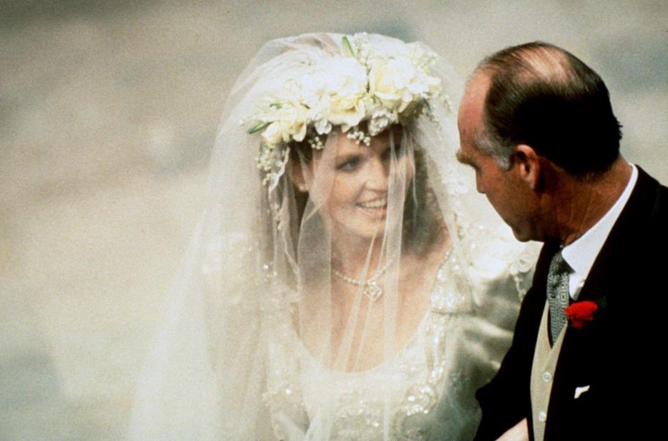"""<p>When Sarah Ferguson headed down the aisle on the arm of her father in 1986, <a href=""""https://www.goodhousekeeping.com/beauty/fashion/a22574019/sarah-ferguson-wedding-crown/"""" rel=""""nofollow noopener"""" target=""""_blank"""" data-ylk=""""slk:she wore a gorgeous flower headdress"""" class=""""link rapid-noclick-resp"""">she wore a gorgeous flower headdress</a>. After she signed her marriage certificate, she removed it and revealed the stunning brand-new York tiara, especially commissioned for the wedding and gifted by the Queen, according to <em><a href=""""https://www.express.co.uk/life-style/life/942985/sarah-ferguson-fergie-wedding-prince-andrew"""" rel=""""nofollow noopener"""" target=""""_blank"""" data-ylk=""""slk:Express"""" class=""""link rapid-noclick-resp"""">Express</a></em>. The ceremonial removal of the flowers symbolized Fergie's official entrance into the royal family. </p>"""