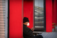 A man wearing a face mask to protect against the spread of the coronavirus uses his cellphone at a public park in Beijing, Tuesday, Feb. 2, 2021. China has largely stopped domestic transmission of the virus through sometimes draconian measures, including strict testing and electronic surveillance. Mask wearing in public is standard and lockdowns are routinely imposed on communities and even entire cities where cases are detected. (AP Photo/Mark Schiefelbein)