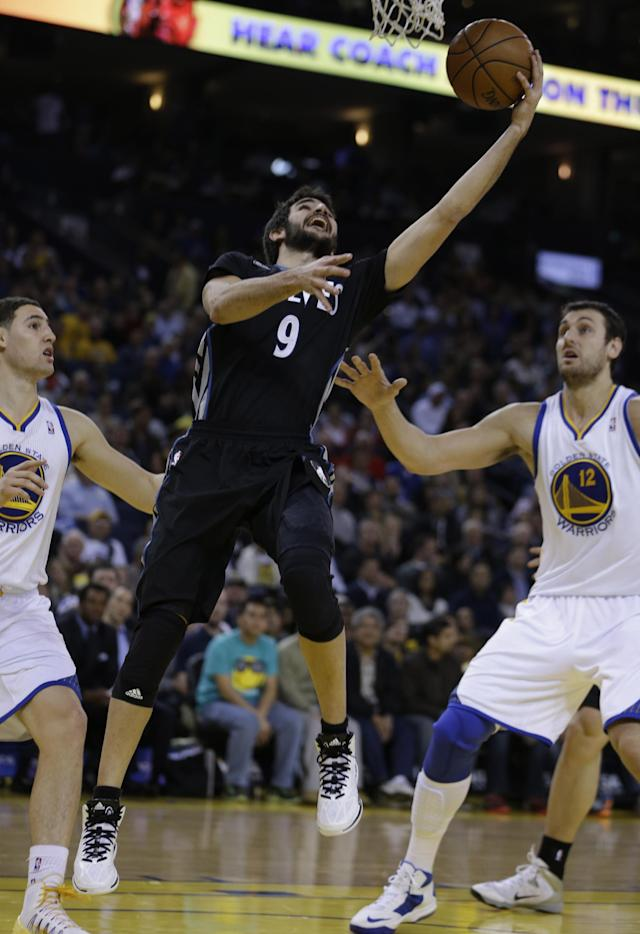 Minnesota Timberwolves' Ricky Rubio (9) lays up a shot between Golden State Warriors' Klay Thompson, left, and Andrew Bogut (12) during the second half of an NBA basketball game Friday, Jan. 24, 2014, in Oakland, Calif. (AP Photo/Ben Margot)