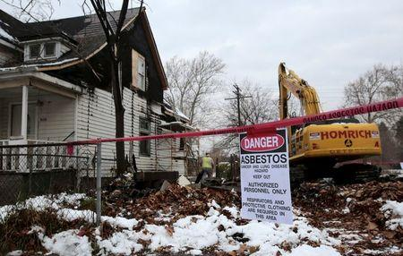 "A ""Danger Asbestos"" sign is seen as a demolition crew removes the remains of a demolished home, next to an occupied one, in a neighborhood filled with blight in Detroit, Michigan, November 24, 2015.  REUTERS/Rebecca Cook"