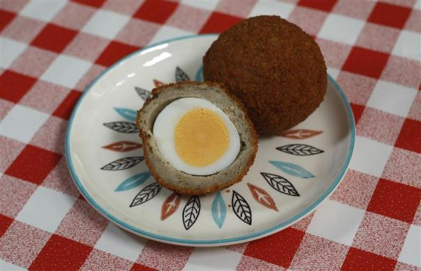 A traditional British snack of a boiled egg wrapped in sausage meat, called a Scotch Egg.