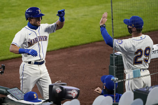 Seattle Mariners' Sam Haggerty, left, is greeted at the dugout by manager Scott Servais, right, after hitting a two-run home run against the Texas Rangers during the fifth inning of a baseball game, Sunday, Aug. 23, 2020, in Seattle. (AP Photo/Ted S. Warren)