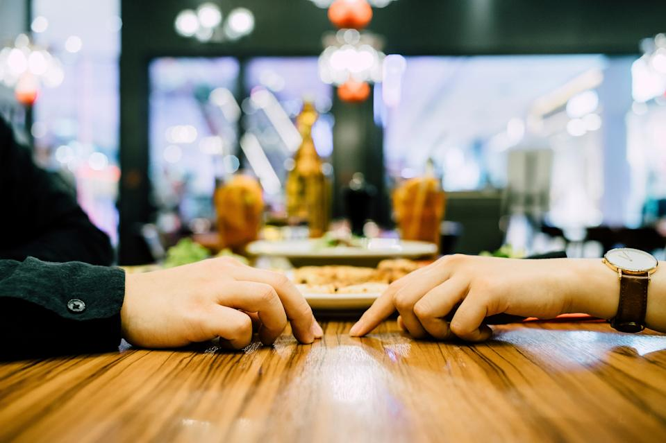 Two hands almost touch across restaurant table in coronavirus age