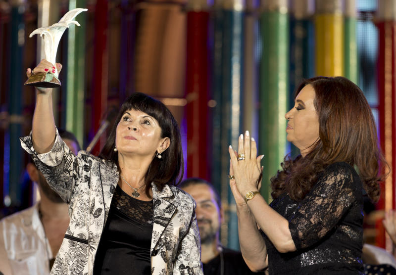 "President Cristina Fernandez, right, applauds as Susana Trimarco, left, lifts a human rights prize given by the president during a rally to mark the 29th anniversary of the return to democracy in Argentina, on the eve of the Human Rights Day, in Buenos Aires, Argentina,  Sunday, Dec. 9, 2012. Trimarco is known for her crusade to find her daughter, Maria de los Angeles ""Marita"" Veron, who disappeared in 2002, and who is believed to had been kidnapped by human traffickers. (AP Photo/Victor R. Caivano)"