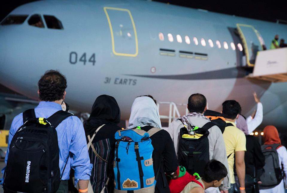 Afghan citizens board a military plane at Abu Dhabi airport on Thursday (AP)