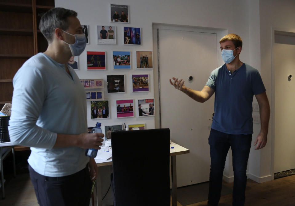 Brothers, Bradford, left, and Bryan Manning, stand in their New York City loft discussing the origins of their clothing company, Two Blind Brothers, on Friday, Oct. 23, 2020. The brothers who've lost much of their vision to a rare degenerative eye disorder began their company in 2016 and have donated all profits, more than $700,000, to preclinical research trials to help cure blindness. (AP Photo/Jessie Wardarski)