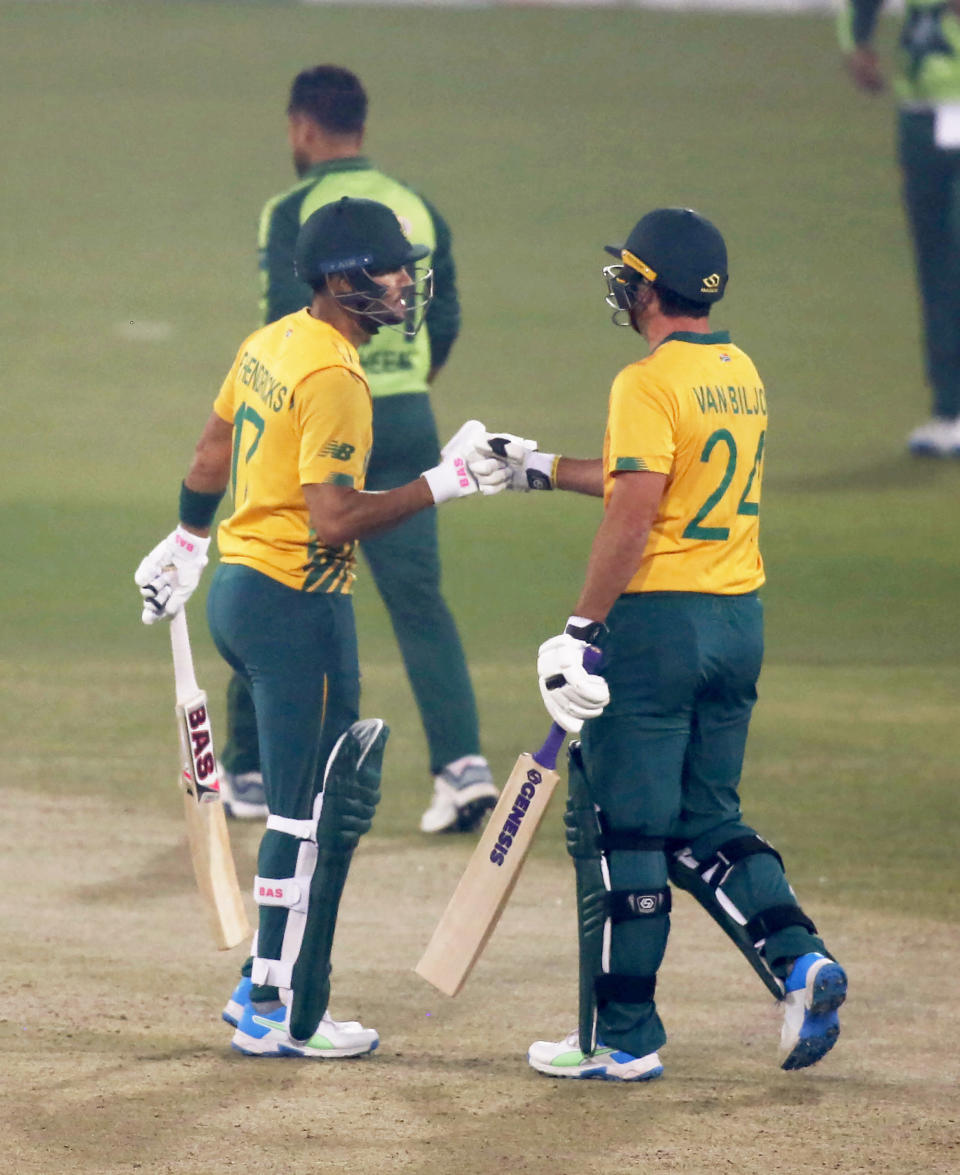 South Africa's Pite van Biljon, right, celebrates with teammate Reeza Hendricks after hitting a boundary during the 2nd Twenty20 cricket match between Pakistan and South Africa at the Gaddafi Stadium, in Lahore, Pakistan, Saturday, Feb. 13, 2021. (AP Photo/K.M. Chaudary)