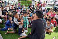 There's no quiet rule at this open-air reading park wedged between two lanes of traffic just outside Indonesia's capital