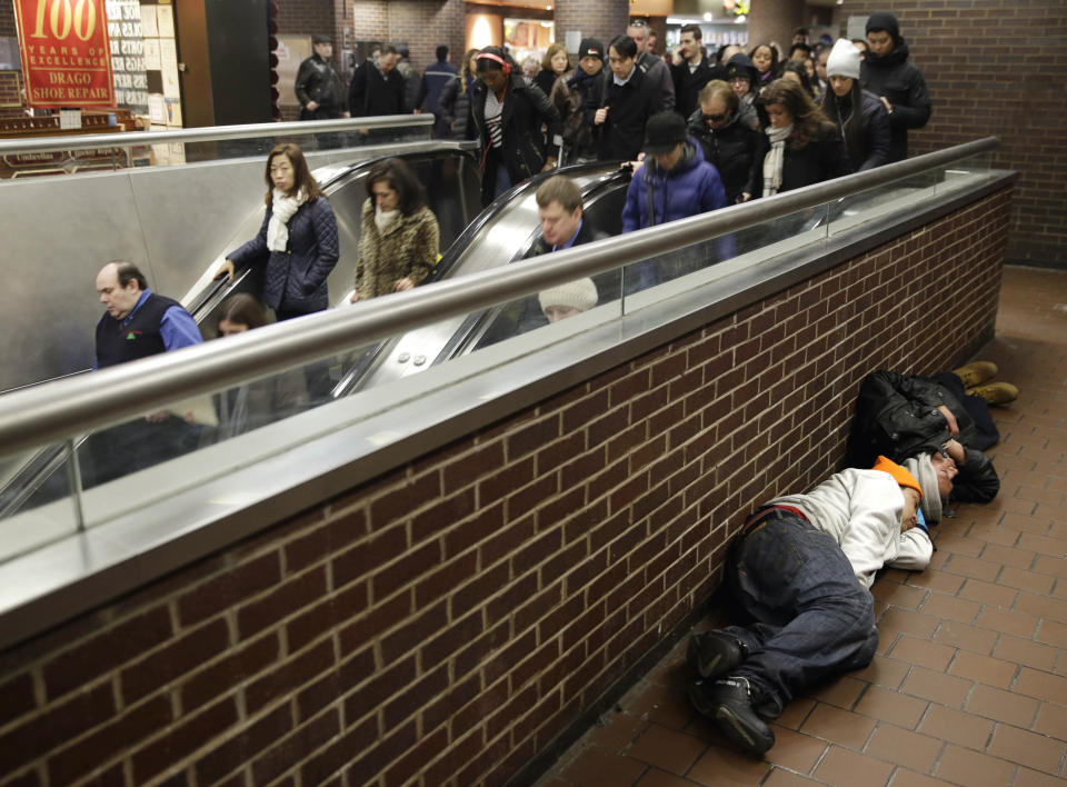 FILE — In this Mach 19, 2015 file photo, two men sleep on the floor of the Port Authority Bus Terminal in New York. New York City's main bus terminal, long ridiculed for leaky ceilings, dirty bathrooms and frequent delays, could be in for a major overhaul. The Port Authority of New York and New Jersey unveiled a plan Thursday, Jan. 21, 2021, to rebuild and expand the embattled midtown Manhattan bus terminal. (AP Photo/Seth Wenig, File)