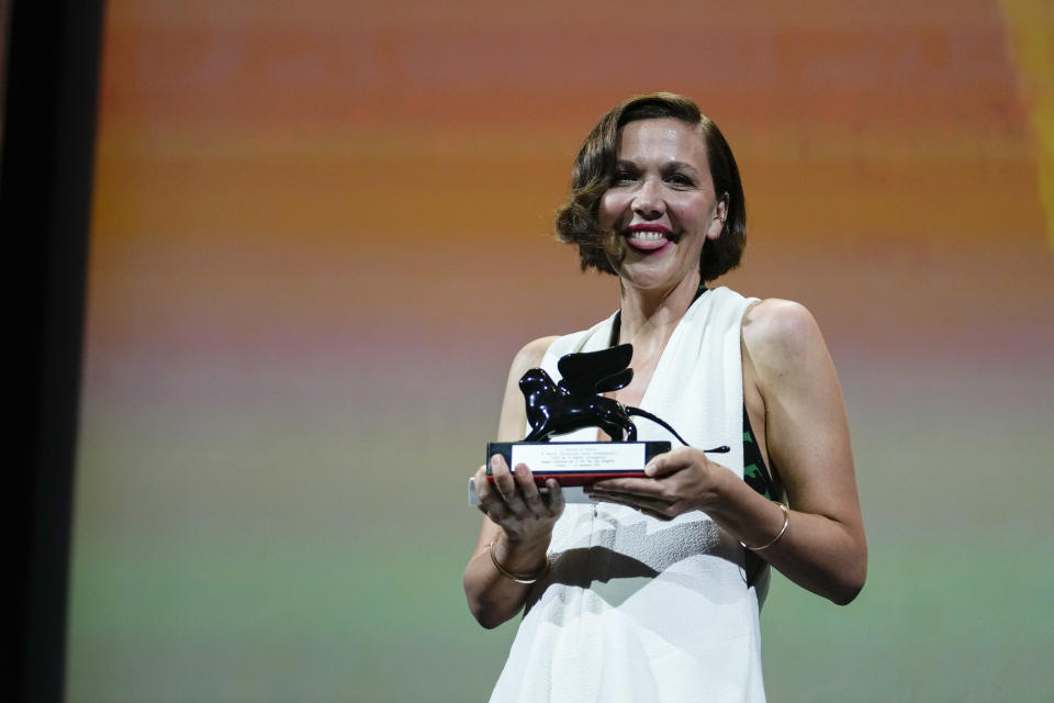 FILE - In this Sept, 11, 2021 file photo Maggie Gyllenhaal holds the Best Screenplay award for 'The Lost Daughter' onstage at the closing ceremony during the 78th edition of the Venice Film Festival in Venice, Italy. (AP Photo/Domenico Stinellis, File)