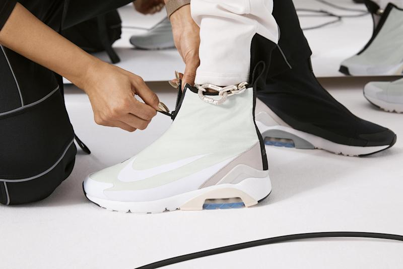 A person fitting a fashionable-looking Nike high-top sneaker on another person's foot.