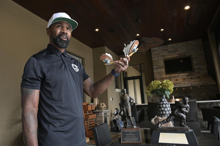 Former NFL football player Charles Woodson stands with his collegiate Jim Thorpe Award, Heisman Trophy and clubfoot brace shoes during an interview at his home Tuesday, June 15, 2021, in Orlando, Fla. Growing up in Fremont, Ohio, Woodson overcame the deformity and went on to become a first-ballot Pro Football Hall of Famer, who will be inducted about 100 miles from his hometown on Sunday, Aug. 8. (AP Photo/Phelan M. Ebenhack)