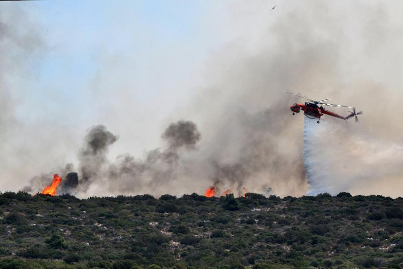 In this Sunday, Aug. 19, 2012 photo a firefighting helicopter drops water over a burning forest on the Greek eastern Aegean Sea island of Chios. Hundreds of firefighters, soldiers and volunteers were struggling for a third day Monday to tame a massive fire that burnt some 7,000 hectares of forest, cultivated land and groves of the island's famed mastic trees. Smoke from the blaze, which was swept on by gale-force winds, was carried as far as the southern island of Crete, more than 350 kilometers (230 miles) away. (AP Photo/Icon Press) GREECE OUT