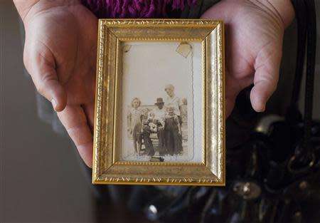 Terri Evans of Manning, South Carolina holds a photograph taken around 1943 that shows members of her family including murder victim Mary Emma Thames (far left) at a hearing to reopen the case of George Stinney, Jr., in Sumter, South Carolina, January 21, 2014. REUTERS/Randall Hill