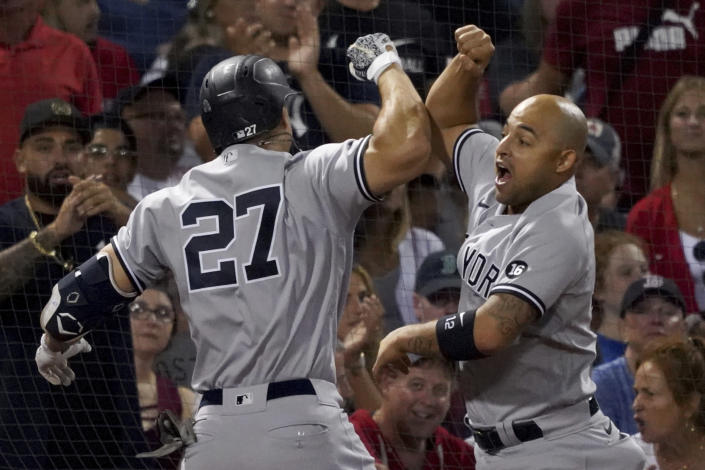 New York Yankees designated hitter Giancarlo Stanton (27) celebrates with teammate Rougned Odor after hitting a three-run home run during the third inning of a baseball game against the Boston Red Sox at Fenway Park, Friday, Sept. 24, 2021, in Boston. (AP Photo/Mary Schwalm)