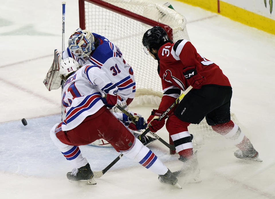 New York Rangers goaltender Igor Shesterkin (31) makes a save with Rangers center Brett Howden (21) helping on defense and New Jersey Devils Nicholas Merkley (39) threatening during the second period of an NHL hockey game, Tuesday, April 13, 2021, in Newark, N.J. (AP Photo/Kathy Willens)