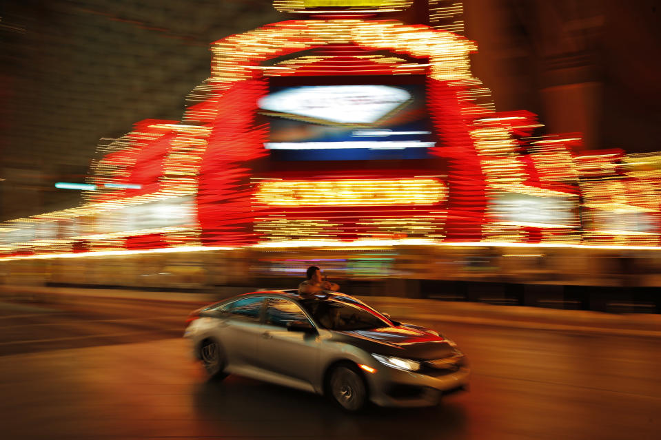 In this April 21, 2020, photo taken with a slow shutter speed, a person takes pictures of temporarily closed casinos from the sunroof of a car in downtown Las Vegas. The usual crowds have been replaced by the occasional bicyclist or driver marveling at the quiet and empty streets. (AP Photo/John Locher)