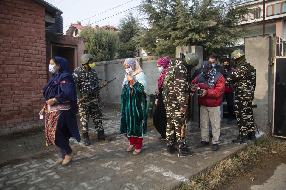 Soldiers stand guard as Kashmiris enter a polling booth area to cast their votes during the first phase of District Development Councils election on the outskirts of Srinagar, Indian controlled Kashmir, Saturday, Nov. 28, 2020. Thousands of people in Indian-controlled Kashmir voted Saturday amid tight security and freezing cold temperatures in the first phase of local elections, the first since New Delhi revoked the disputed region's semiautonomous status. (AP Photo/Mukhtar Khan)
