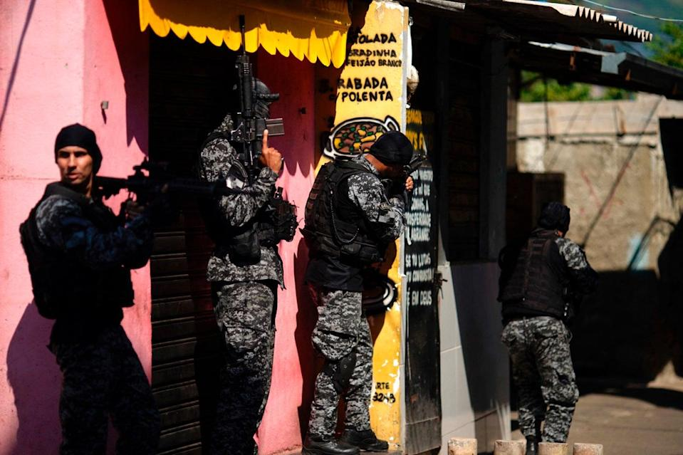 <p>Police officers carry out a raid against drug traffickers in the Jacarezinho area of Rio de Janeiro</p> (AFP via Getty Images)