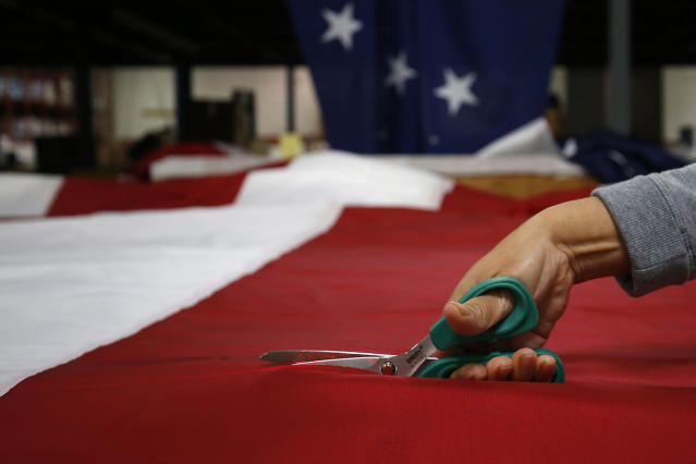<p>A worker trims an American flag at the FlagSource facility in Batavia, Illinois, U.S., on Tuesday, June 27, 2017. (Photo: Jim Young/Bloomberg via Getty Images) </p>