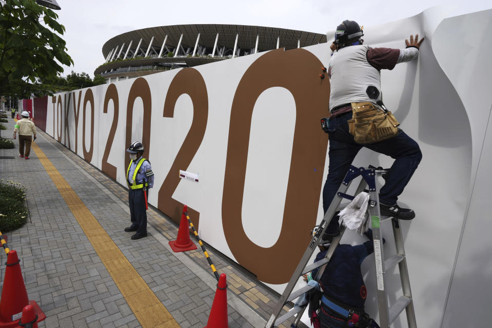 Workers paste the overlay on the wall of the National Stadium, where opening ceremony and many other events are scheduled for the postponed Tokyo 2020 Olympics, Wednesday, June 2, 2021, in Tokyo. Roads are being closed off around Tokyo Olympic venues including the new $1.4 billion National Stadium where the opening ceremony is set for July 23(AP Photo/Eugene Hoshiko)