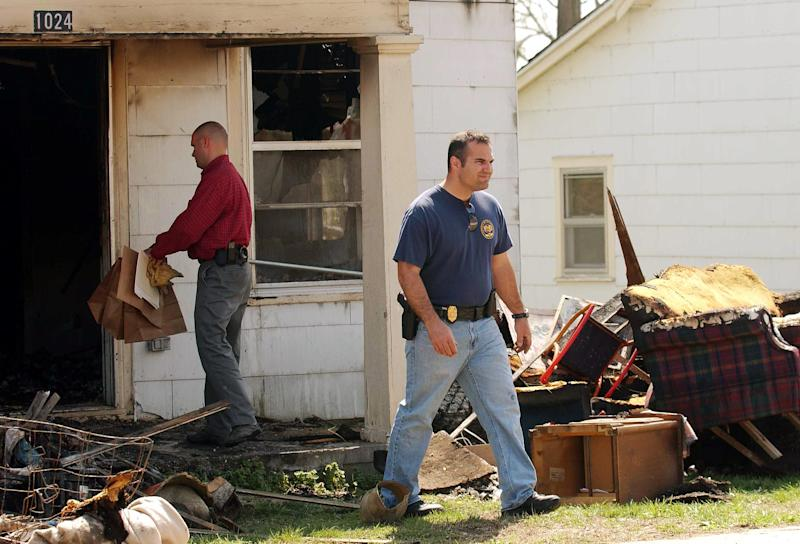In this 2008 photo investigators collect evidence following a fire at a house in Springfield, Mo., where prosecutors said Jeffrey Allen Dickson left his victim, a 7-year-old girl, to die after setting the house ablaze to cover up his crime. The girl survived and a Springfield jury quickly found Dickson guilty of child kidnapping, forcible rape and forcible sodomy in the April 5, 2008 attack. But new evidence unearthed by Dickson's state-appointed appeals court lawyer and reviewed as part of a five-month Associated Press investigation suggests that a rush to judgment could have caused police and prosecutors to target the wrong man. He is scheduled to argue his appeal on Tuesday and Wednesday, Oct. 10, 2012, in Springfield, Mo. (AP Photo/The Springfield News-Leader, Steve J.P.Liang)