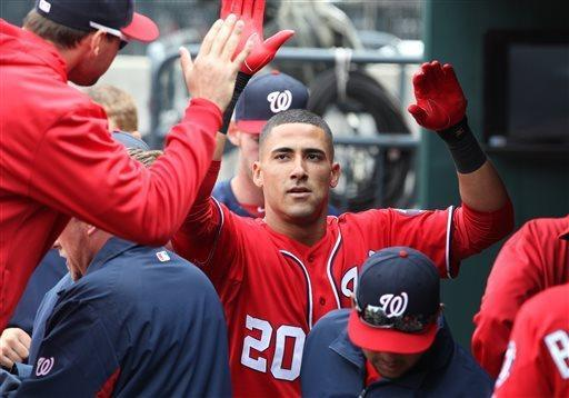 Washington Nationals's Ian Desmond is congratulated in the dugout after hitting a solo home run in the second inning of a baseball game against the New York Mets in New York on Saturday, April 20, 2013. (AP Photo/Peter Morgan)