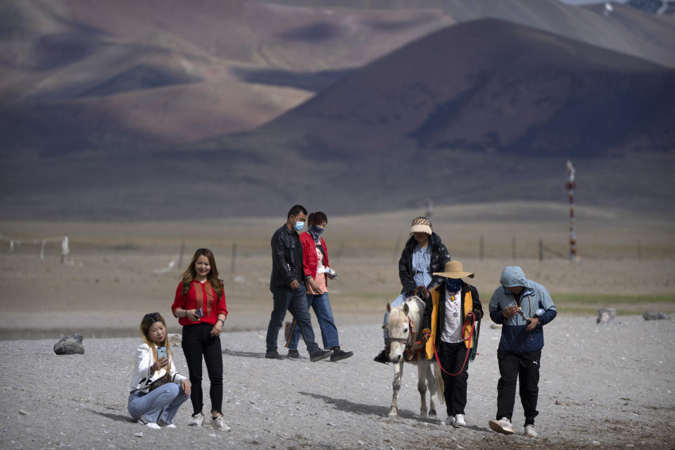 Tourists walk along the lakeshore and ride a pony in Namtso in western China's Tibet Autonomous Region, Wednesday, June 2, 2021. Tourism is booming in Tibet as more Chinese travel in-country because of the coronavirus pandemic, posing risks to the region's fragile environment and historic sites. (AP Photo/Mark Schiefelbein)