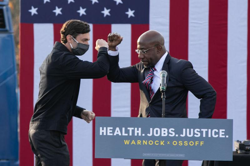 "Georgia Democratic Senate candidates Raphael Warnock (R) and Jon Ossoff (L) bump elbows during a ""It's Time to Vote"" drive-in rally on December 28, 2020 in Stonecrest, Georgia."